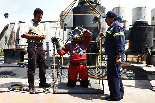 Mexican sewer diver Julio Cu Camara kneels in a cage while putting on his helmet before a dive at the city's drainage system plant in Mexico City